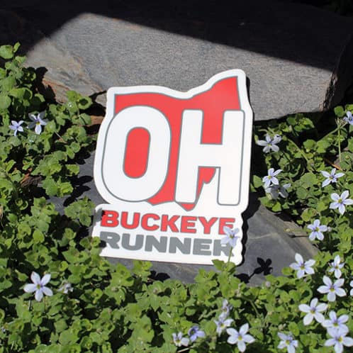 Buckeye Running Sticker laying on rocks with white flowers for website